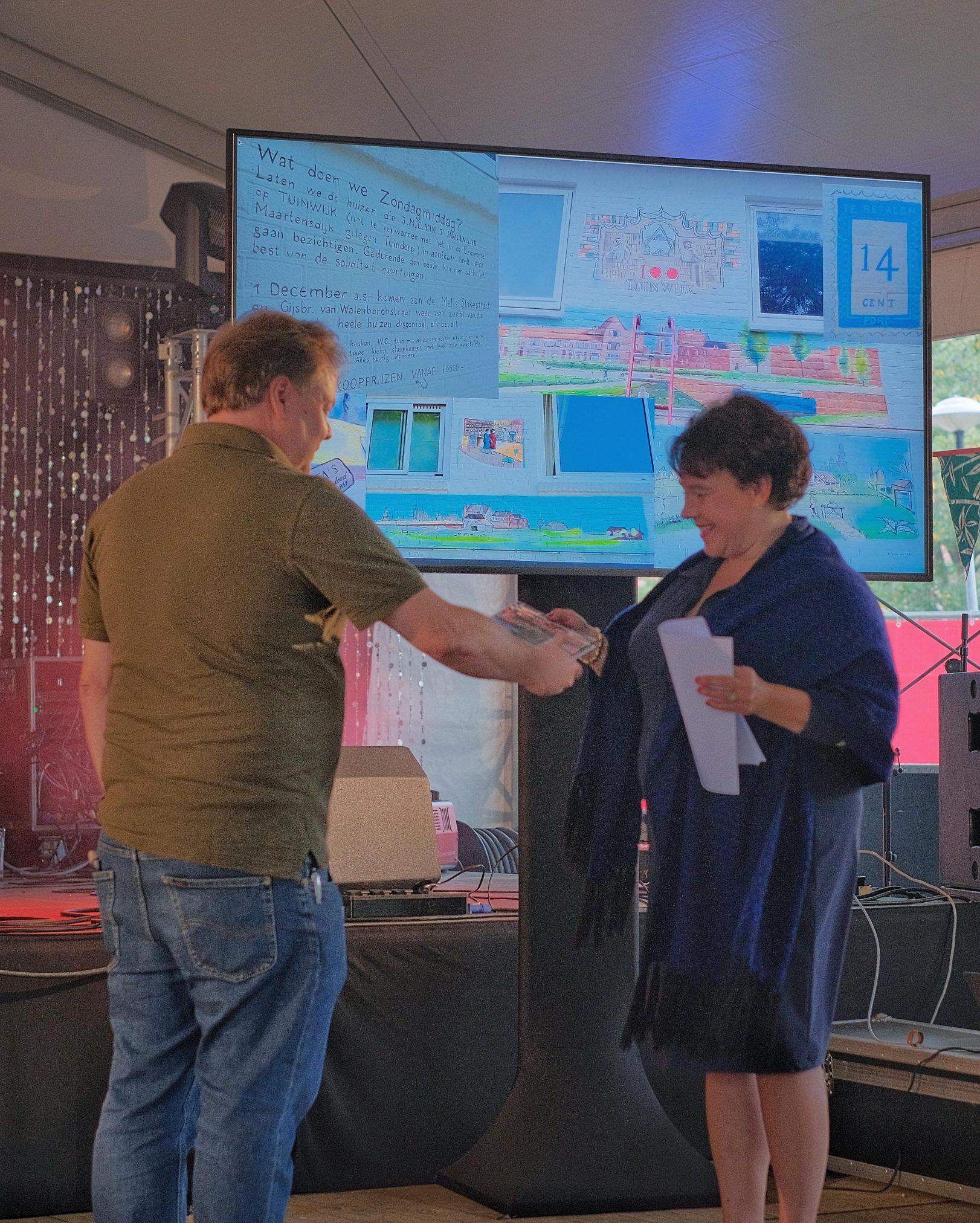 Auteur van gedenkboek 'De Tuinwijk 100, een bijzondere wijk.' Alex van Hout overhandigd het eerste exemplaar aan burgemeester Sharon Dijksma.